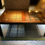 木製のデザイン性の高いテーブルに強化ガラスを置かれたお客様