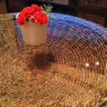 円形の籐テーブルの上にガラスを置かれたお客様