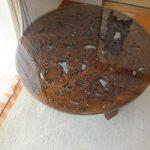 彫刻で装飾された円形テーブルにガラスを置かれたお客様